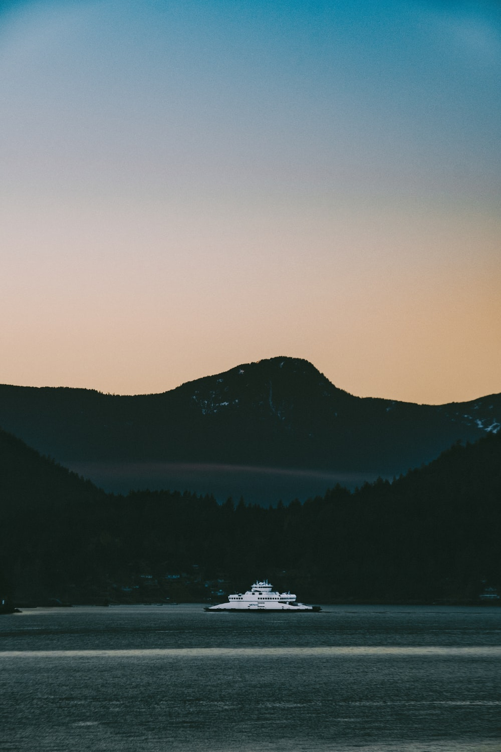 white boat on water near mountain during daytime
