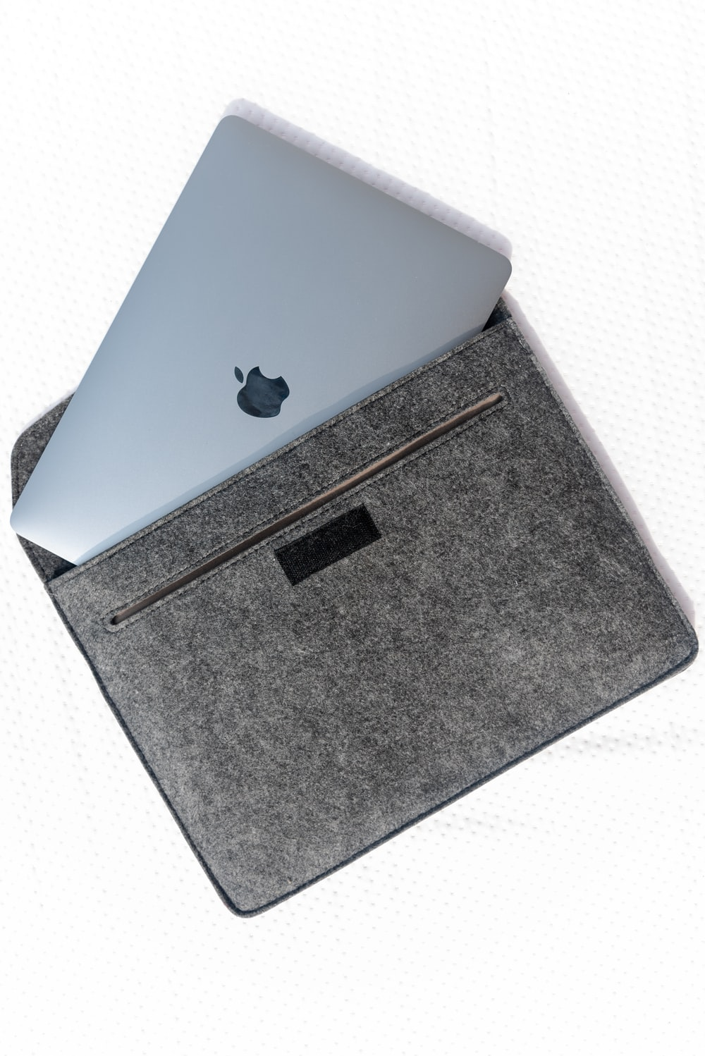 silver macbook on gray textile