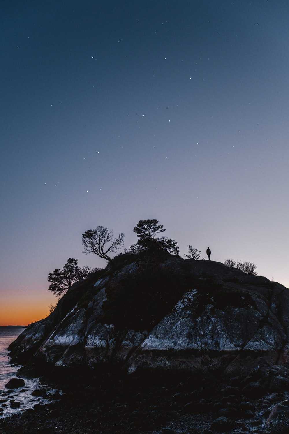 silhouette of 2 people standing on rock formation during night time