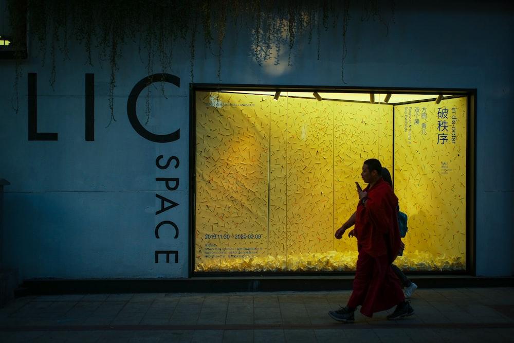 woman in red dress walking on sidewalk during daytime