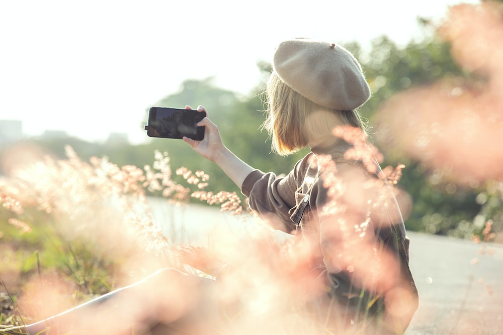 woman in black jacket taking photo of white clouds during daytime