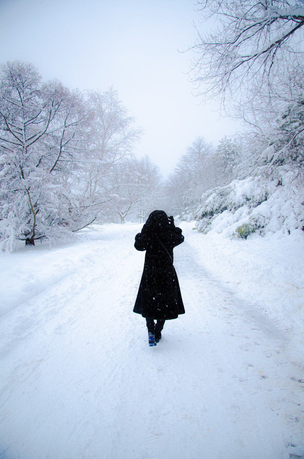 person in black coat walking on snow covered ground during daytime