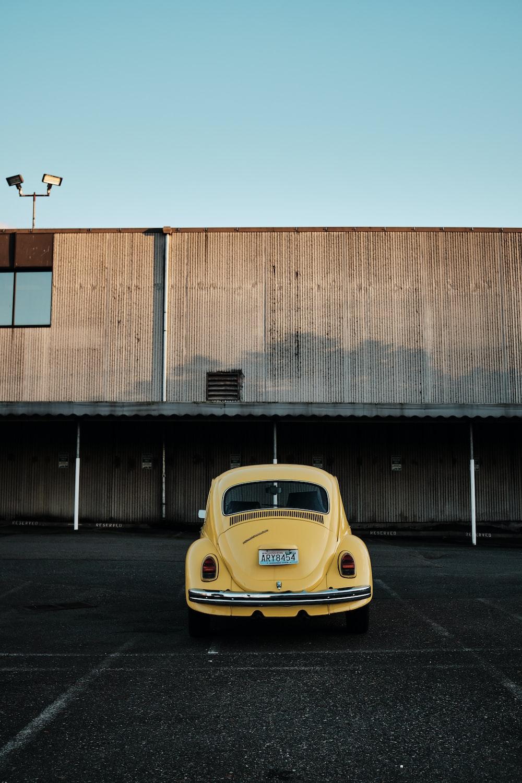 yellow porsche 911 parked beside brown building