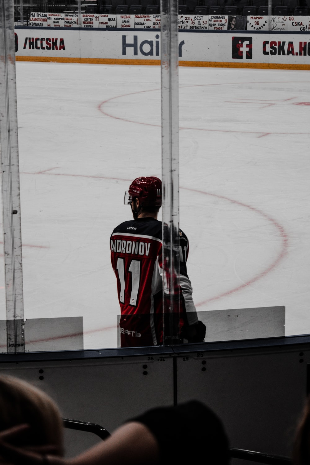 man in red and white jersey shirt and black pants standing on ice hockey field
