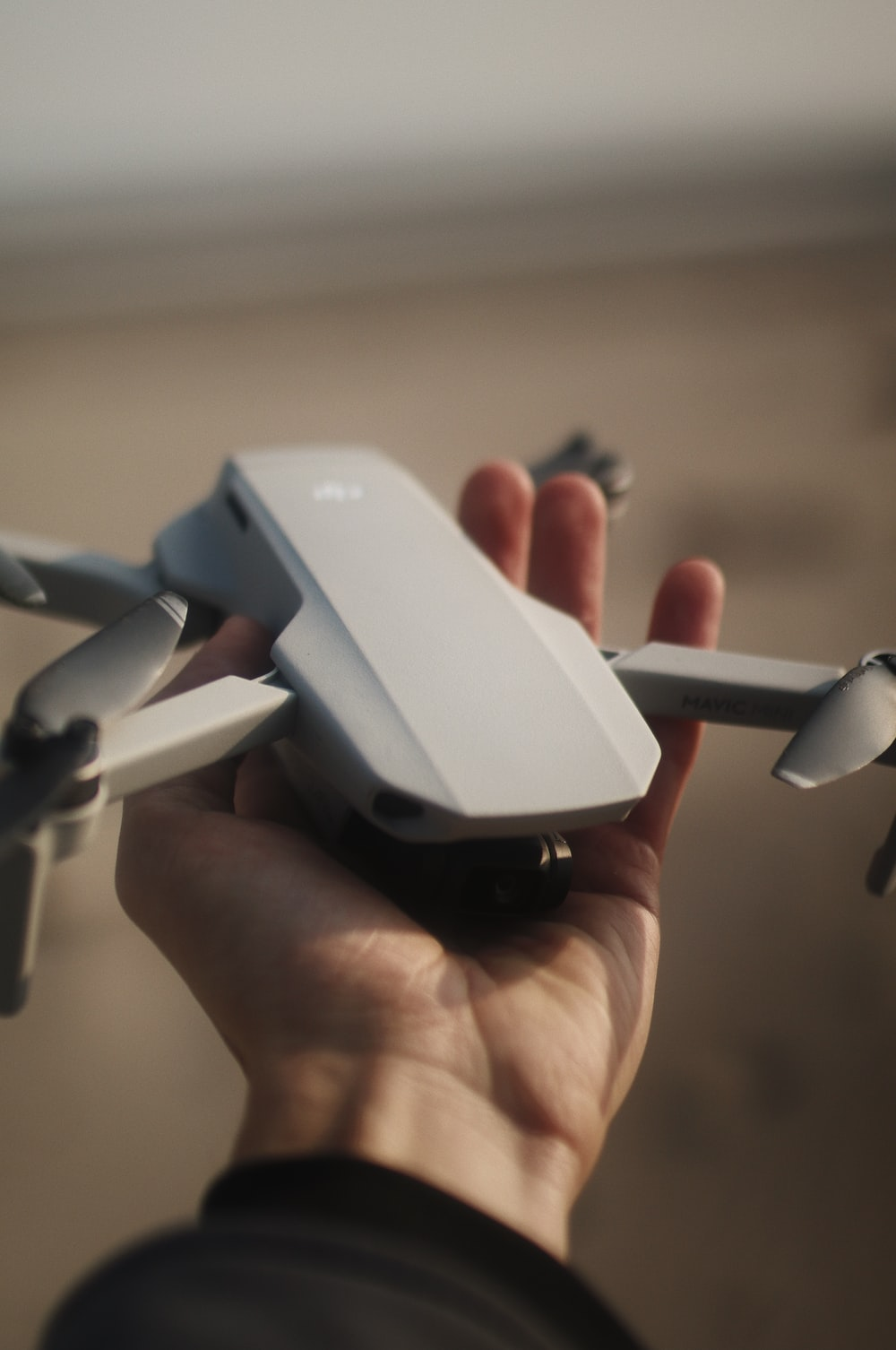 person holding white and black drone