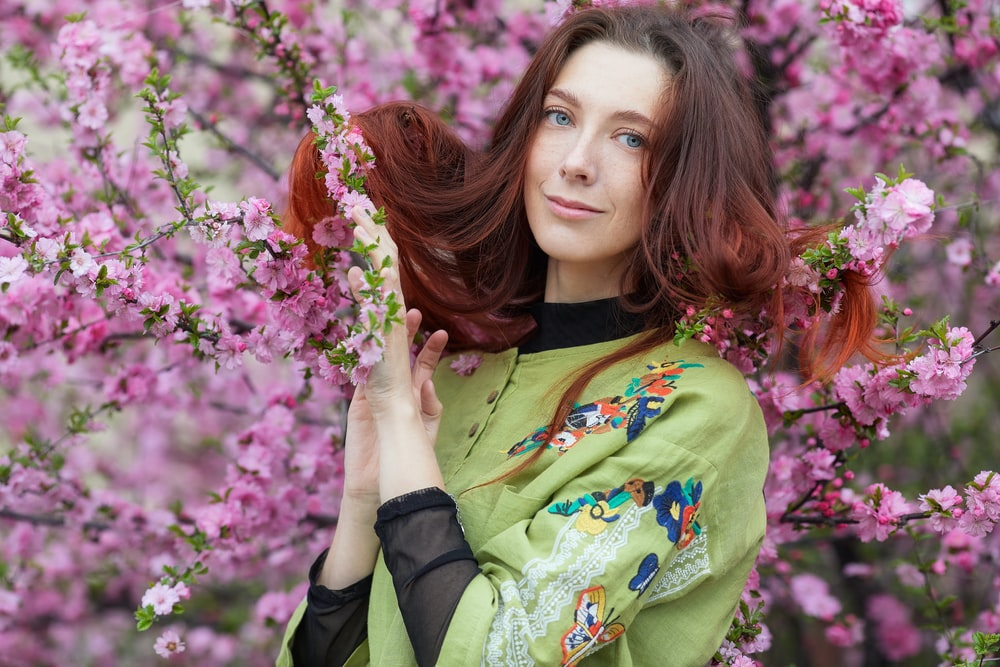woman in green and yellow long sleeve shirt holding pink flowers