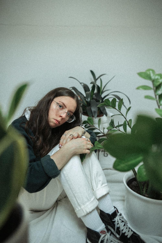 woman in blue long sleeve shirt sitting beside green plant