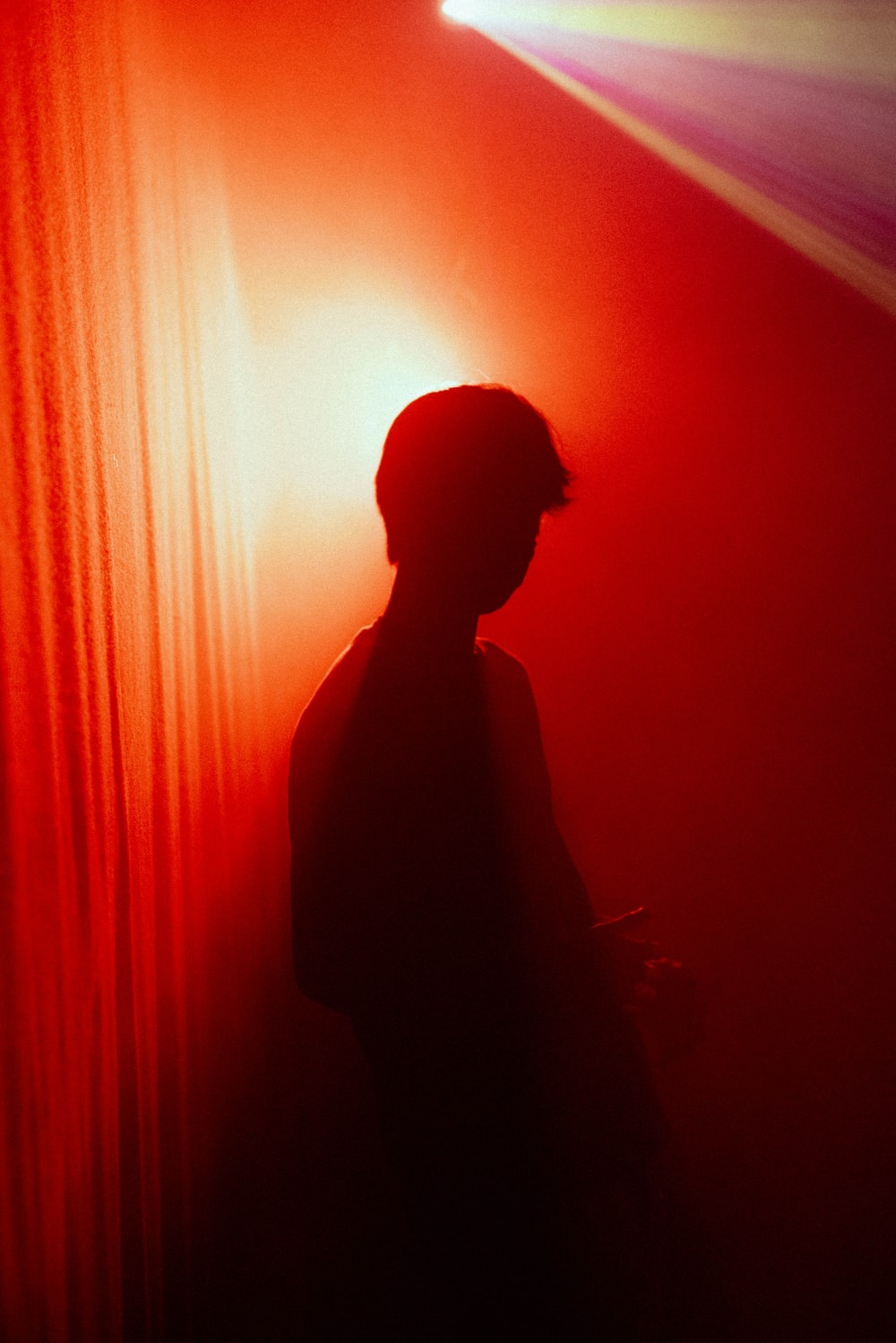 silhouette of man standing near red curtain