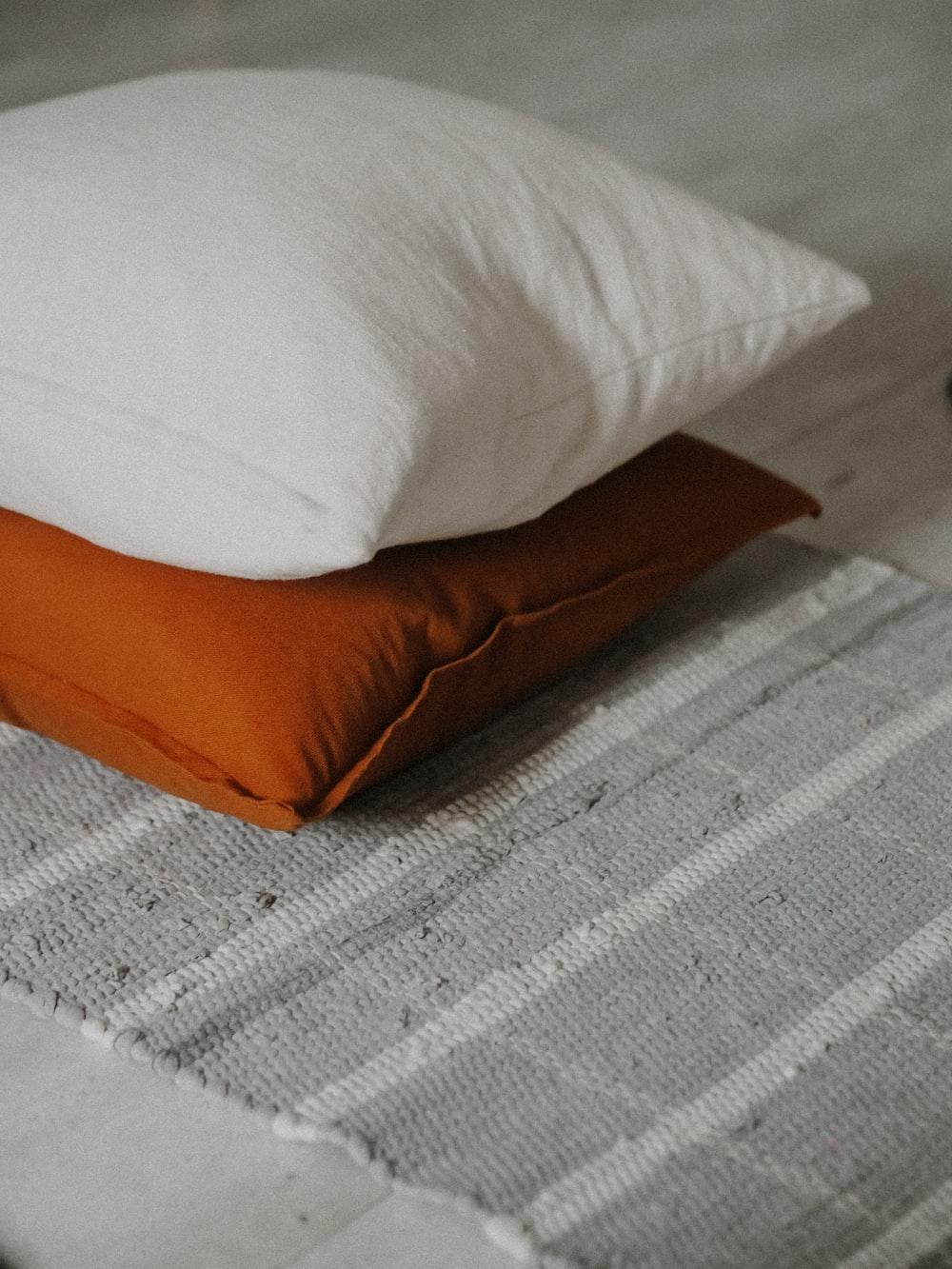 white and brown throw pillow on white textile