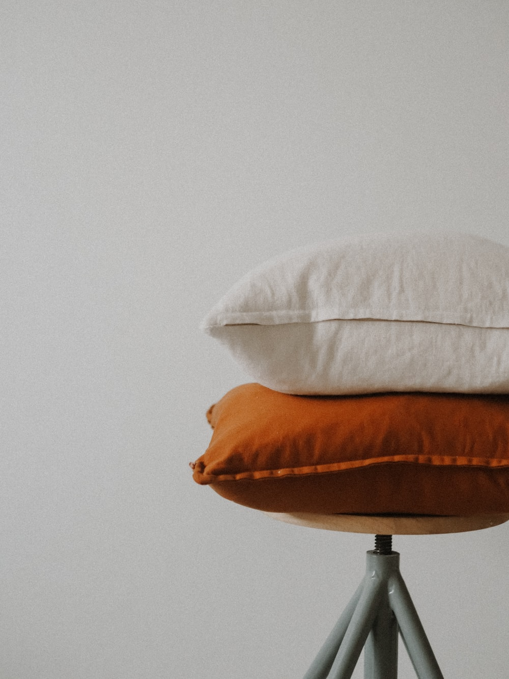 white pillow on brown wooden round table