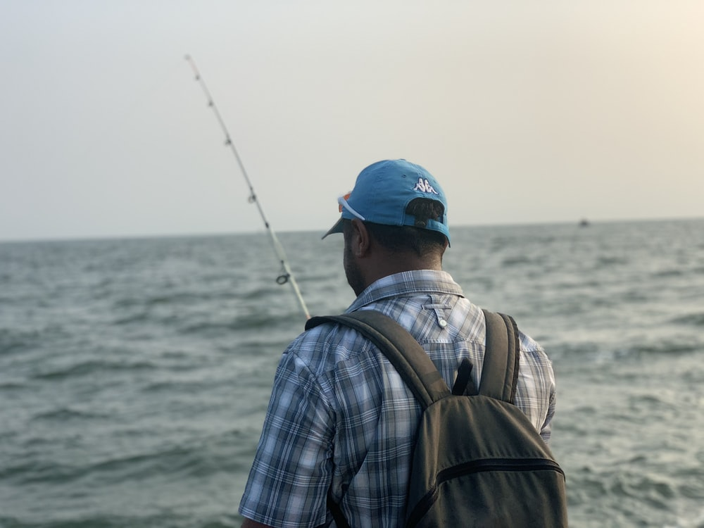 man in blue cap and plaid shirt fishing during daytime