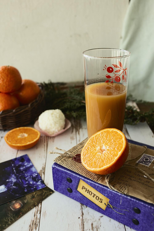 orange juice in clear drinking glass beside sliced orange fruit