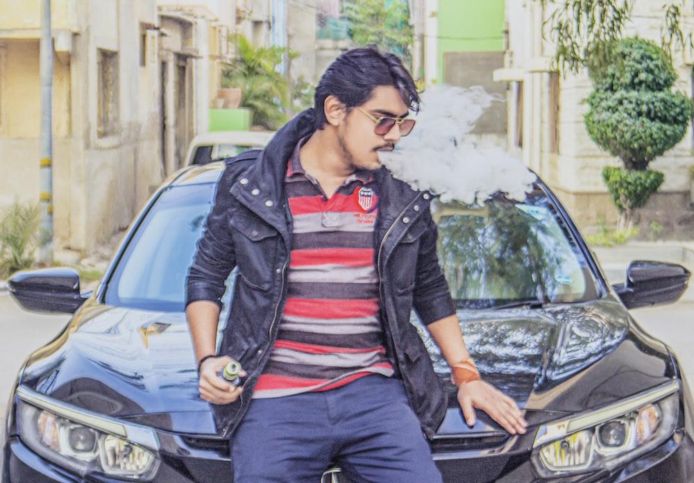 man in black leather jacket sitting on black car