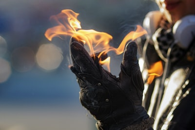 fire in black leather boot burning man teams background