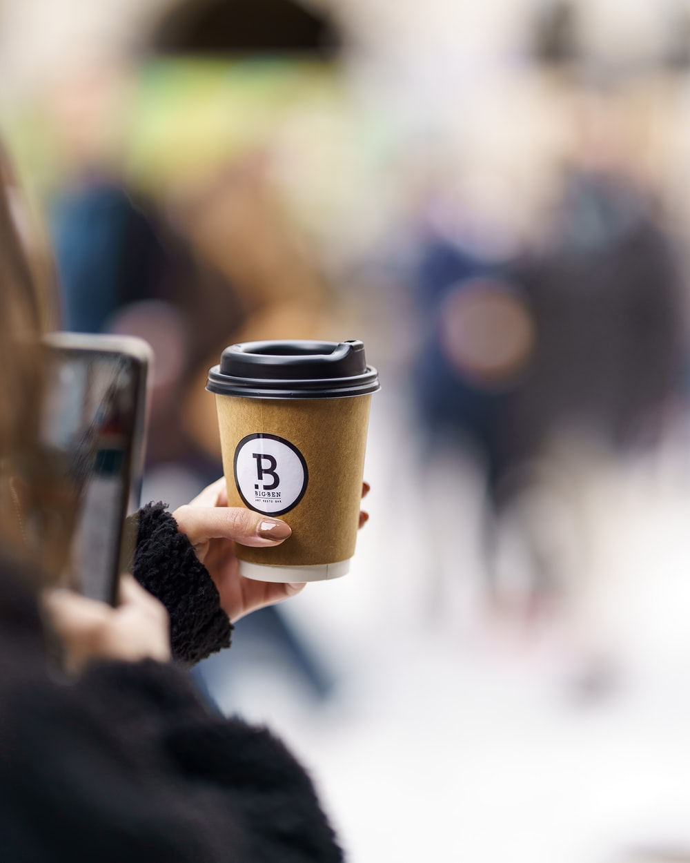 person holding brown and black coffee cup