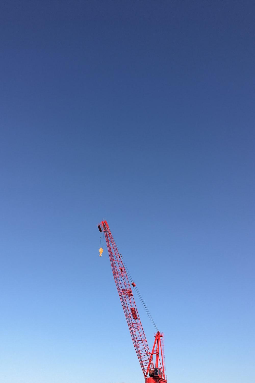 orange crane under blue sky during daytime