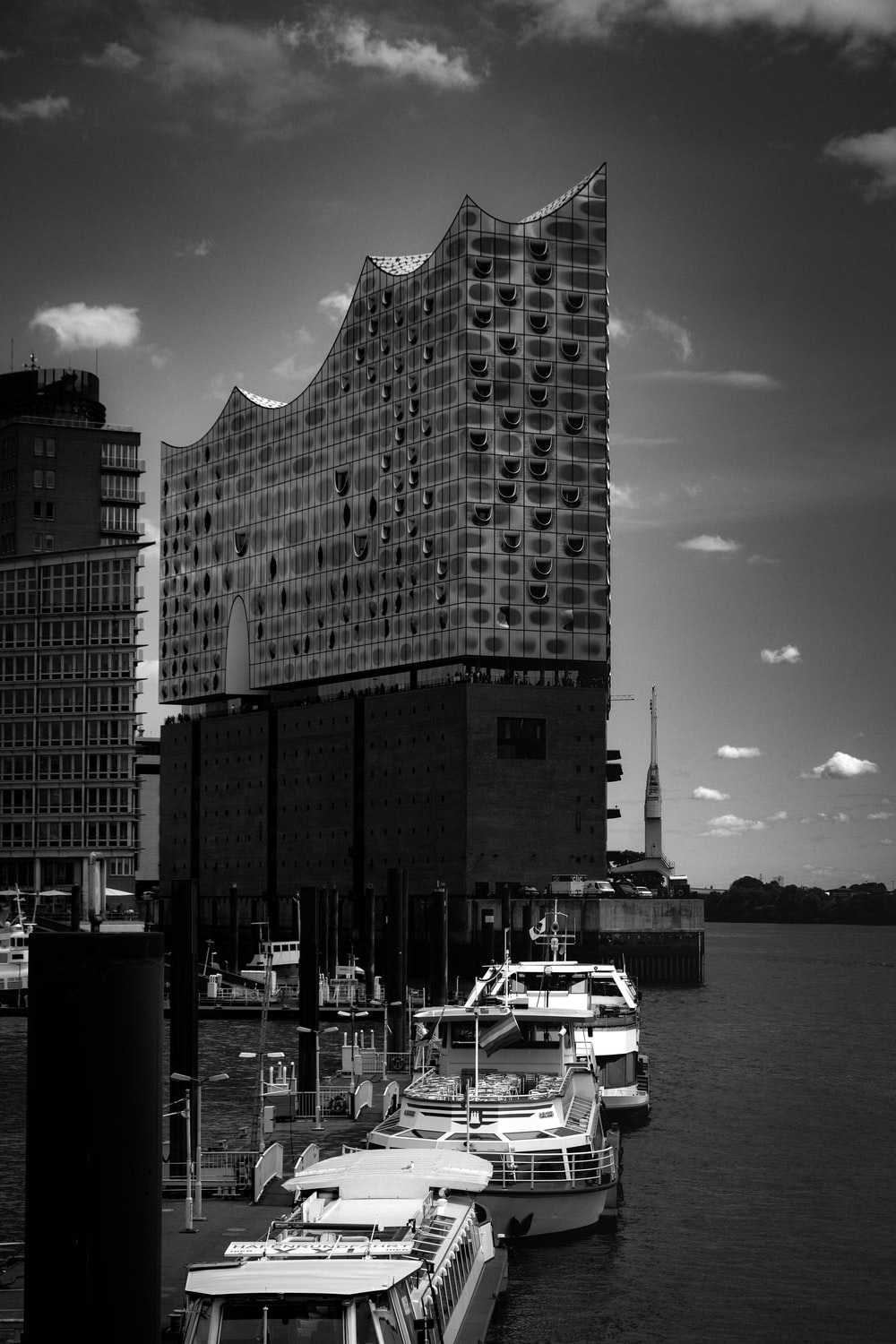 grayscale photo of high rise building near body of water
