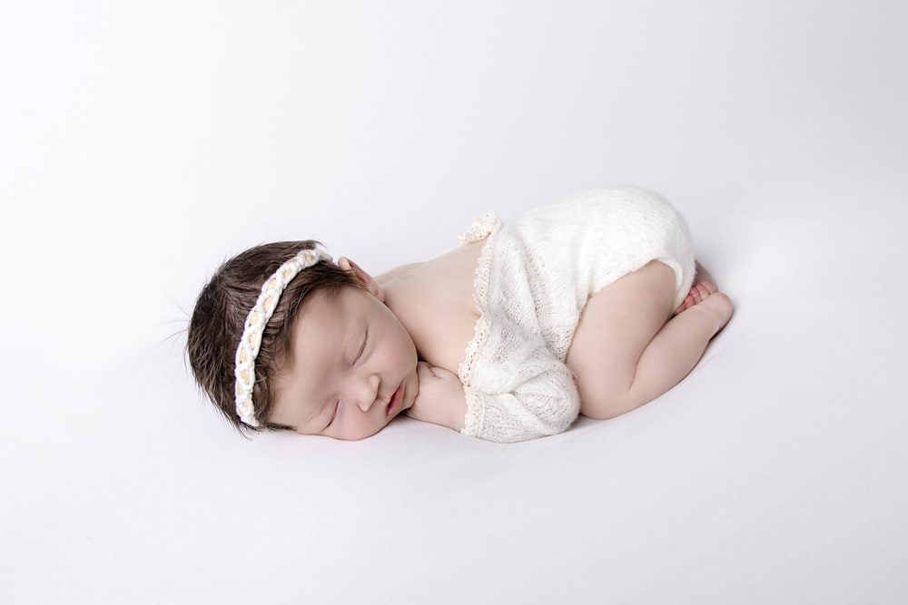 baby in white tank top lying on white bed