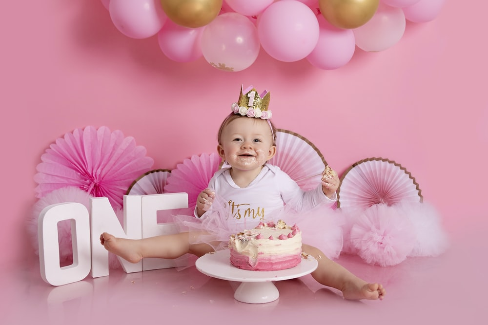 baby in pink long sleeve shirt sitting on pink and white polka dot bed