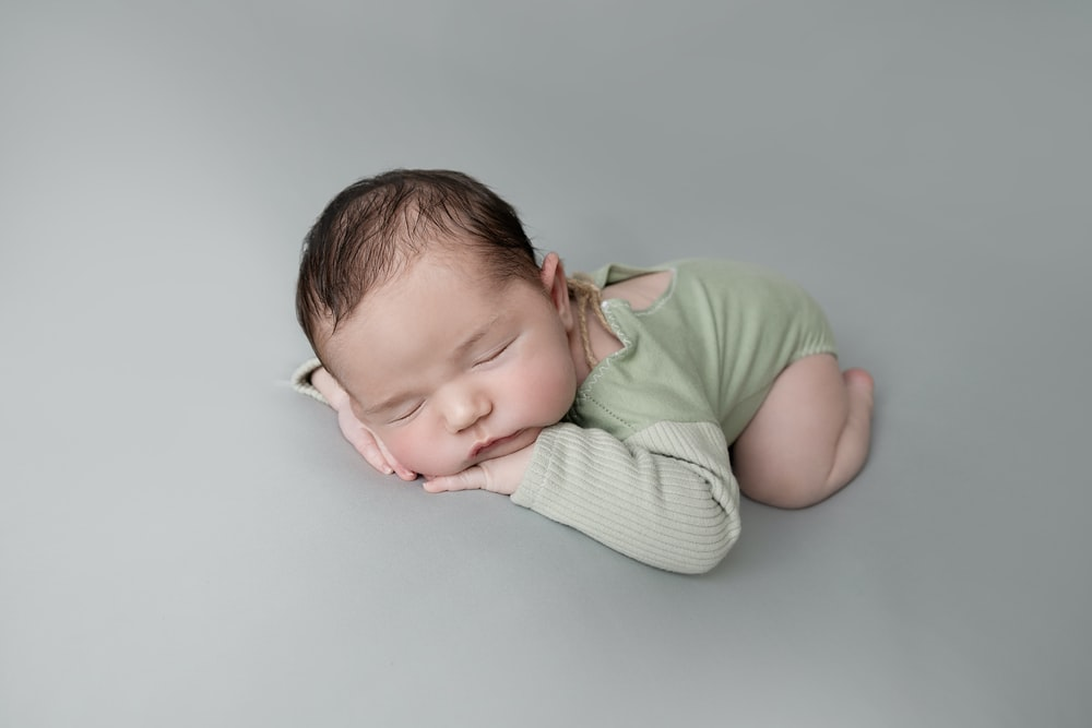baby in green shirt lying on white textile