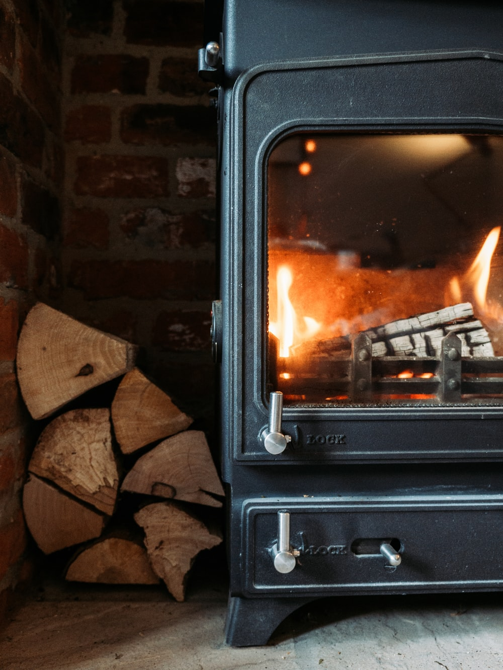 black electric fireplace turned on near brown brick wall