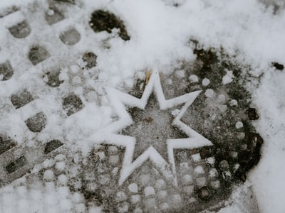 white snow flakes on gray sand