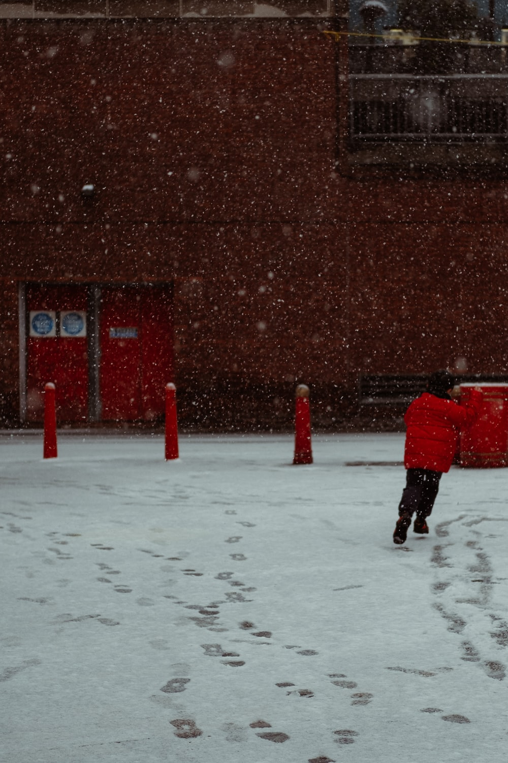 person in red jacket walking on snow covered ground