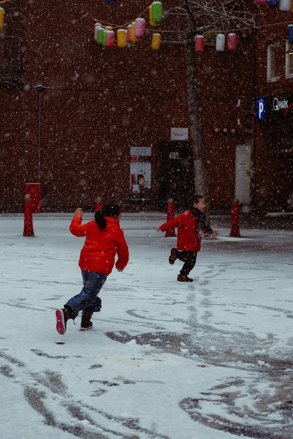 child in red jacket and blue pants walking on snow covered ground during daytime