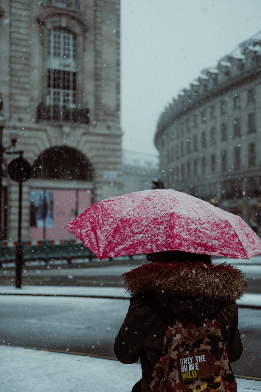 person holding red umbrella walking on sidewalk during daytime