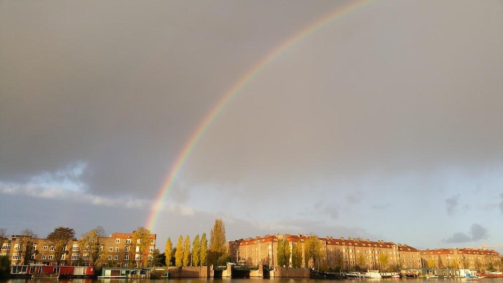 brown concrete building under rainbow