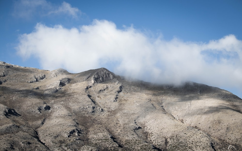 gray mountain under white clouds during daytime