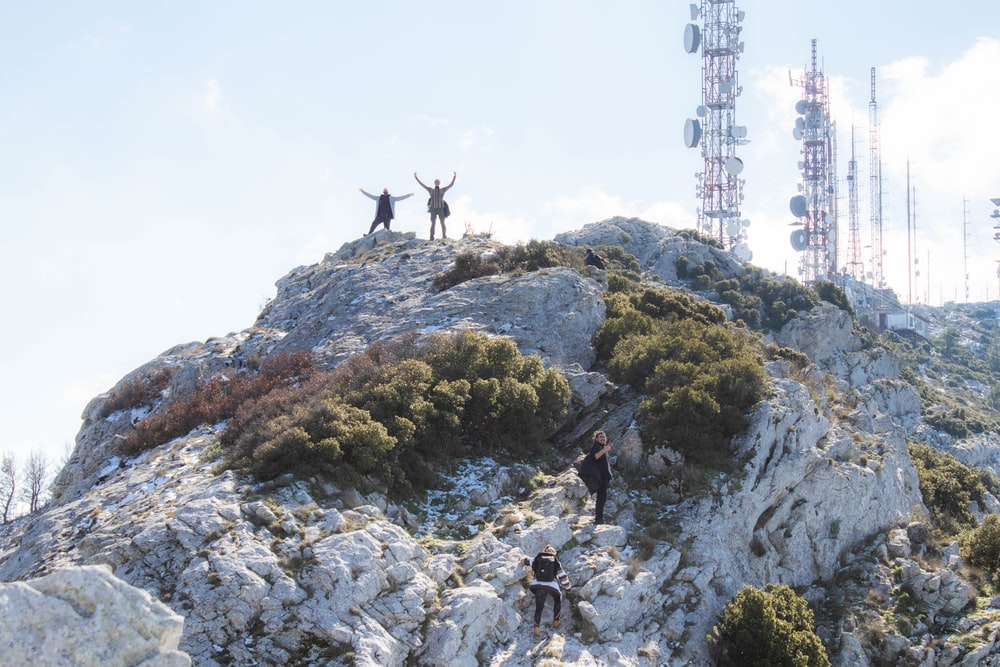 people on top of rocky mountain during daytime