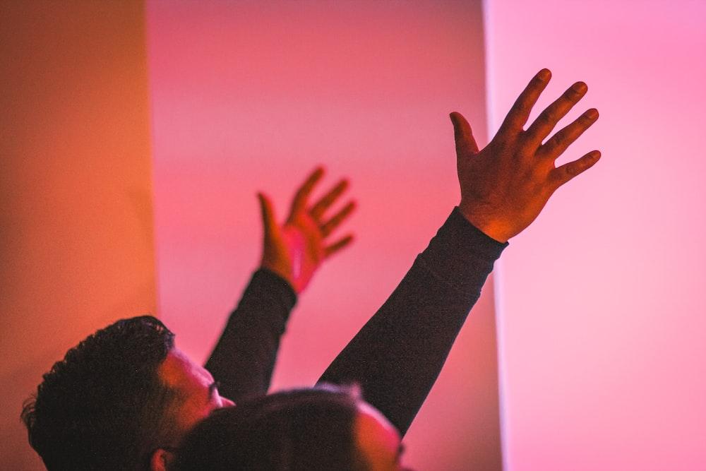 man in black long sleeve shirt raising his hand
