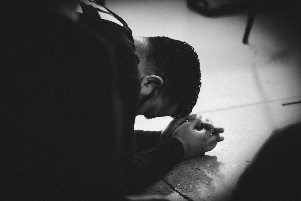 man in black jacket lying on floor