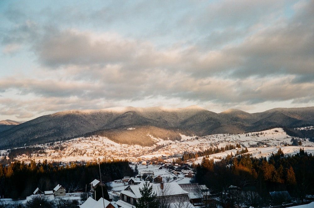white and brown houses near brown mountains under white clouds during daytime