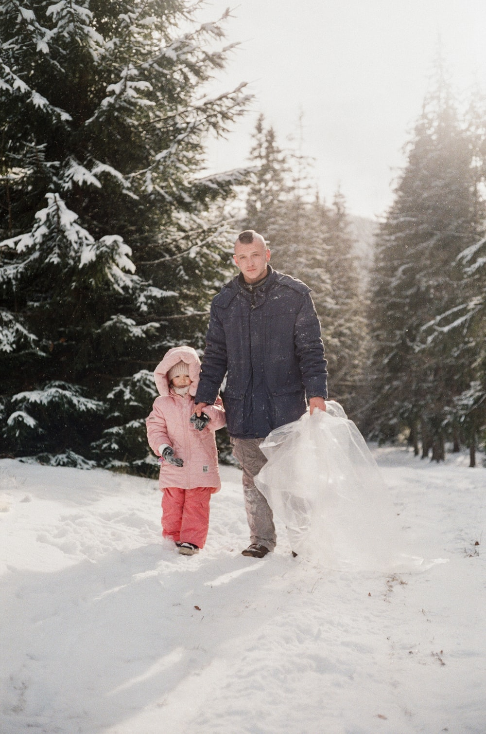 man in black jacket holding girl in pink coat on snow covered ground during daytime