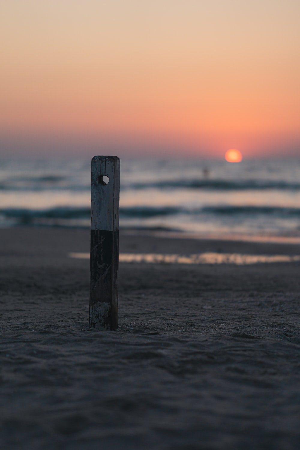 brown wooden post on sea during sunset