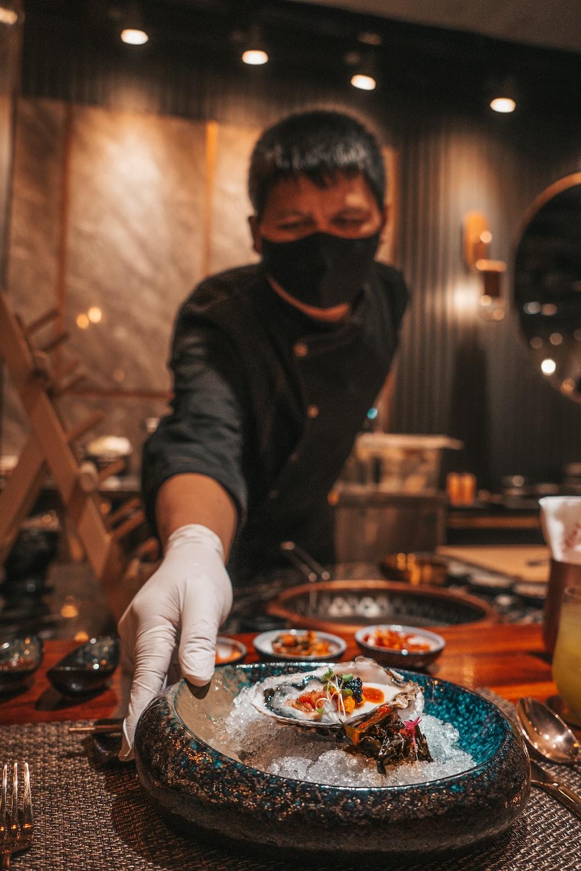 man in black jacket holding black round plate