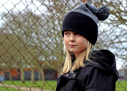 woman in black knit cap and black coat standing near gray metal fence during daytime