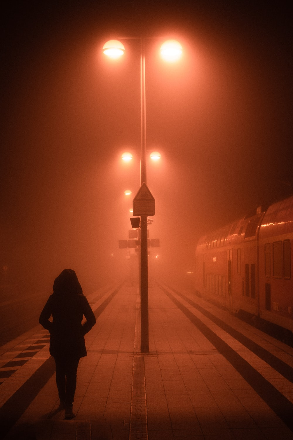 man in black jacket standing near train during night time