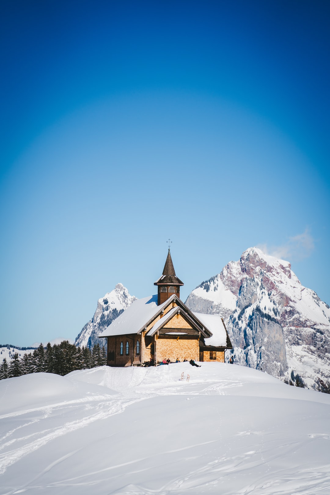 brown wooden church on snow covered ground