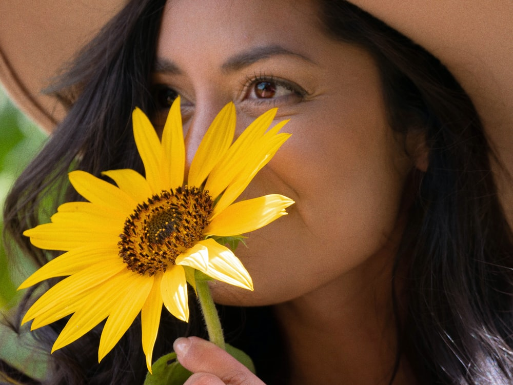 woman with yellow daisy on her ear