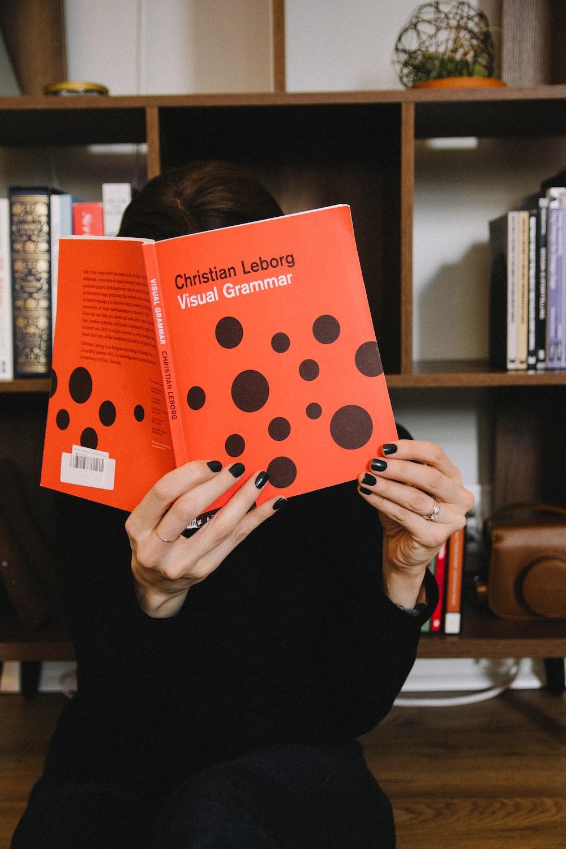 person holding orange and white polka dot paper