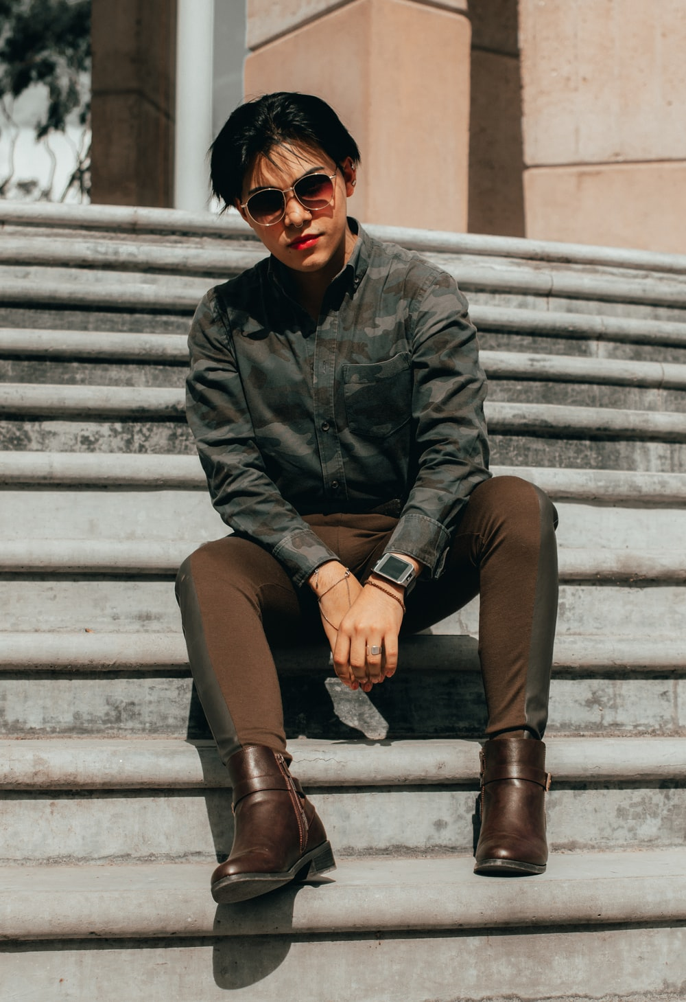 woman in black leather jacket and brown pants sitting on white concrete stairs