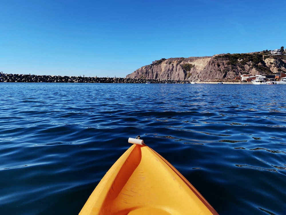 yellow kayak on blue sea near brown and green mountain under blue sky during daytime