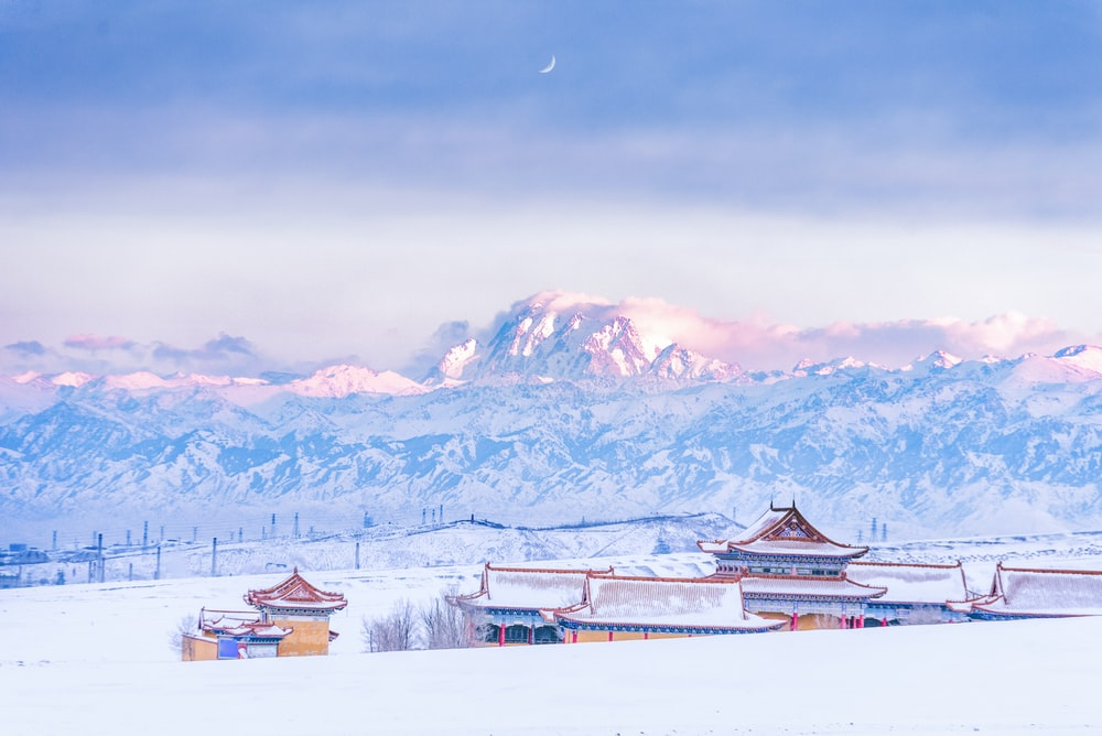 brown wooden houses on snow covered ground near snow covered mountains during daytime