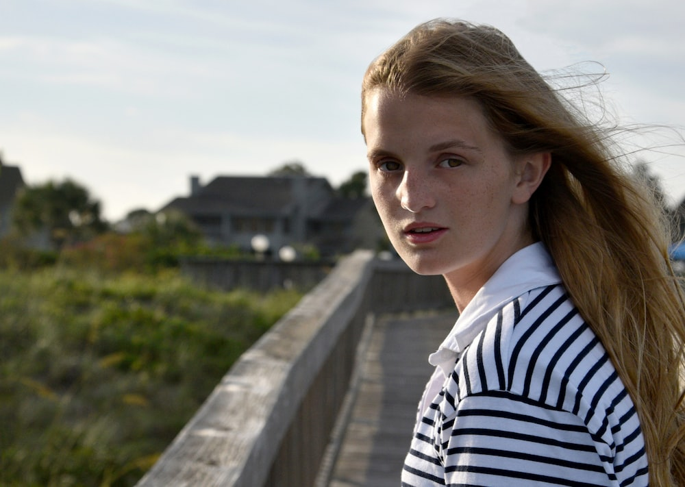 woman in white and black striped shirt standing on gray concrete bridge during daytime