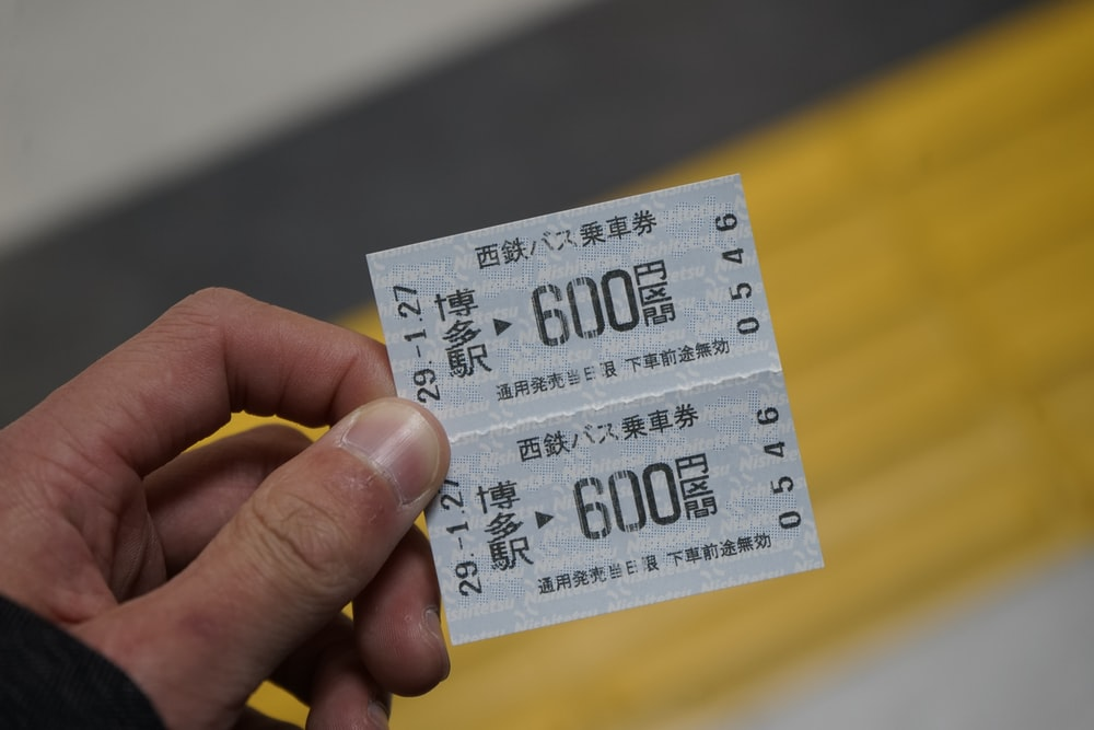 person holding white and black ticket