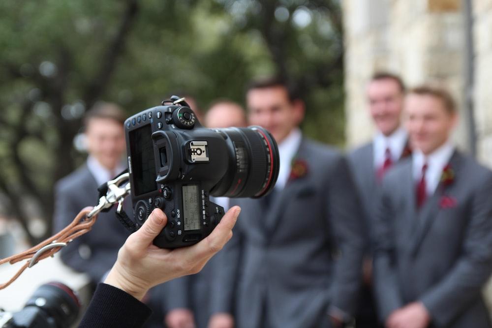 man in black suit holding black nikon dslr camera