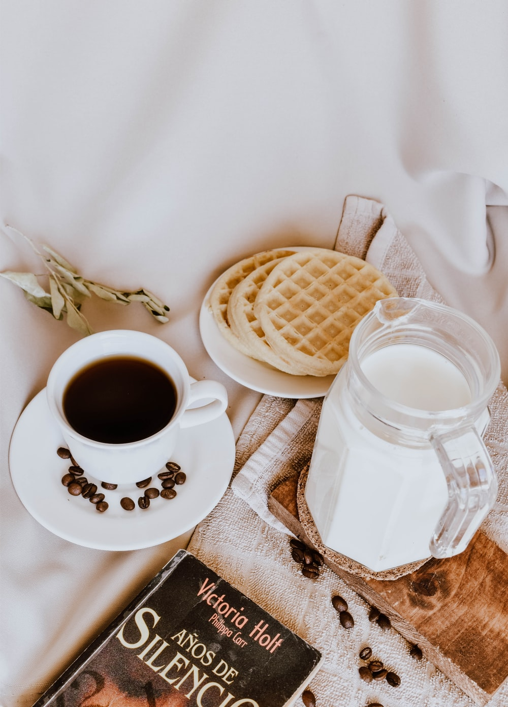 white ceramic mug with coffee beside white ceramic saucer with brown and white cookies